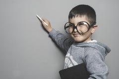 Scolaro, giovane scrittura dello studente su una scuola della lavagna con una b Immagine Stock