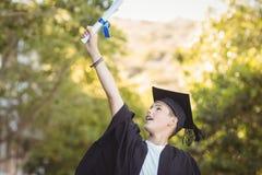 Scolaro laureato emozionante con il rotolo di grado in città universitaria Fotografia Stock Libera da Diritti