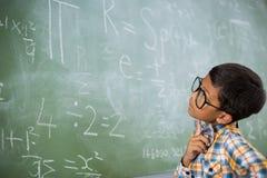 Scolaro premuroso che esamina problema matematico in aula Fotografie Stock Libere da Diritti