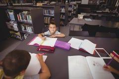 Scolaro sorridente che fa il suo compito in biblioteca Immagine Stock Libera da Diritti