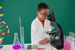Scolaro sorridente che guarda tramite il microscopio in laboratorio Immagini Stock