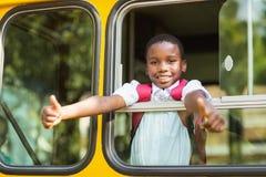 Scolaro sorridente che mostra i pollici su dal bus Fotografie Stock