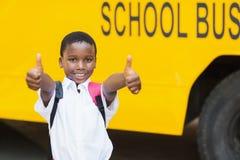 Scolaro sorridente che mostra i pollici su davanti allo scuolabus Immagine Stock