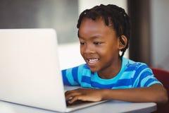 Scolaro sorridente che utilizza computer portatile nell'aula Immagine Stock Libera da Diritti