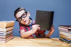 Scolaro sorridente con il libro che si siede allo scrittorio Immagine Stock Libera da Diritti