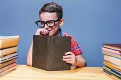 Scolaro sorridente con il libro che si siede allo scrittorio Immagine Stock