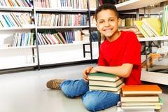 Scolaro sorridente con il mucchio dei libri sul pavimento Fotografia Stock Libera da Diritti