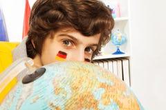 Scolaro tedesco sveglio che si nasconde dietro il globo Fotografia Stock