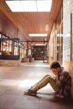 Scolaro triste che si siede da solo in corridoio Immagine Stock Libera da Diritti
