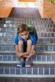 Scolaro triste che si siede da solo sulla scala Fotografia Stock
