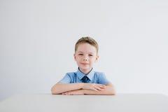 Scolaro in uniforme scolastico che si siede allo scrittorio Fotografia Stock
