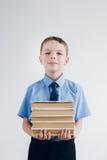 Scolaro in uniforme scolastico che tiene una pila di libri in sua mano Fotografia Stock Libera da Diritti