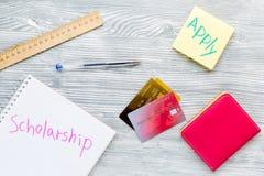 Scolarship si applica con le carte di credito ed il portafoglio sulla vista bianca del piano d'appoggio Immagini Stock Libere da Diritti