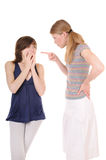 Scolding. One young woman is scolding another girl on white background Stock Photos