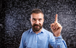 Scolding teacher against big blackboard with mathematical symbol Stock Photos