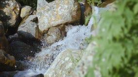 Scoli glaciali dell'acqua attraverso le pietre della montagna archivi video