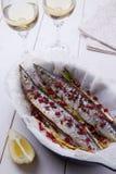 Scombrésoce avec le mélange des poivrons, de l'oignon vert et des graines de grenade avec deux verres de vin blanc Image stock
