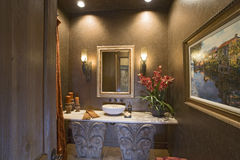 Sconces And Mirror Over Bathroom Sink. Lit sconces and mirror over designed bathroom washbasin stock photos
