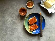 Scone распространил с маслом и маслом яблока, на плите с ножом Стоковые Фото