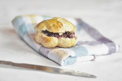 Scone. Fluffy scone filled with unsalted butter and raspberry jam royalty free stock photos
