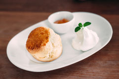 Scone with clotted cream and jam. A delicious scone with clotted cream and jam on white plate Stock Photography