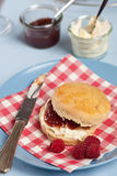 Scone with clotted cream and raspberry jam. Freshly baked scone with raspberry jam and clotted cream Stock Image