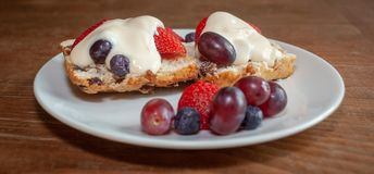 Scone with Fresh Fruit and Cream Panorama. Fruited scone and cream with strawberries, grapes and blueberries on a white plate on wooden table from side, panorama Stock Image