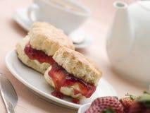 Scone-Marmelade gerann Sahne und Erdbeeren mit Tee Stockfotografie