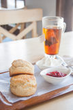 Scone set with tea. Scone and strawberry jam set with hot tea Royalty Free Stock Images