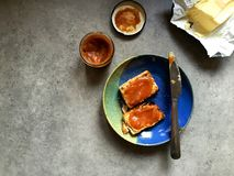 Scone spread with butter and apple butter, on plate with knife Stock Photos
