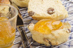 Scone spread with butter and orange jam Royalty Free Stock Photos