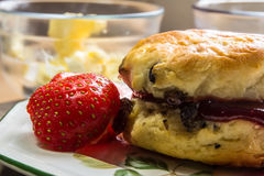 Scone with Strawberry. Still Life of a Scone and Strawberry with dish of butter in the background Stock Photos