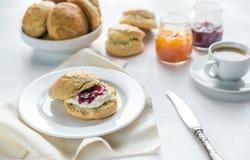Scones с сливк и вареньем и чашкой кофе плодоовощ Стоковые Изображения