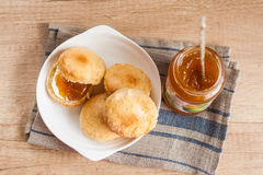 Scones with butter and jam on a napkin and Bank of jam Stock Photography