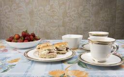 Scones con el atasco, el té y las fresas en una tabla Imagen de archivo