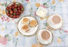 Scones con el atasco, el té y las fresas en una tabla Foto de archivo