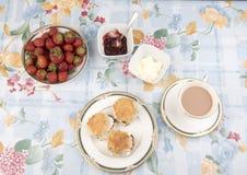Scones con el atasco, el té y las fresas en una tabla Fotos de archivo