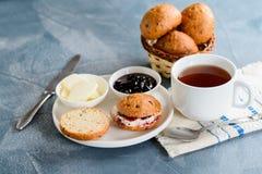 Scones con mantequilla y atasco con té imagen de archivo libre de regalías