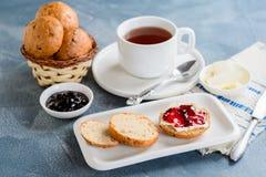 Scones con mantequilla y atasco con té foto de archivo libre de regalías