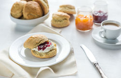 Scones with cream and fruit jam and cup of coffee Stock Images