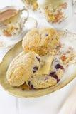 Scones da uva-do-monte com manteiga e um copo do chá Fotografia de Stock Royalty Free