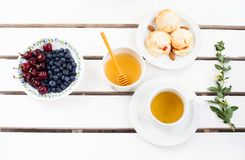 Scones, fruits and tea. Scones, tea and fresh fruit on wooden white table Stock Image