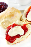 Scones with Jam and Cream. Fresh scones with strawberry jam and fresh cream, served with a cup of tea.  Known as a Devonshire tea or cream tea Stock Images