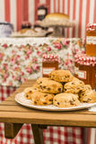 Scones and jam jars. A pile of scones with raisins and jam jars in the background Stock Image