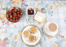 Scones with jam, tea and strawberries on a table stock photos
