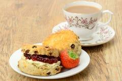 Scones poner crema del té y una taza de té Imagenes de archivo