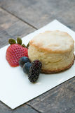 Scones with strawberries, blueberry and mulberry on wooden table Stock Photos