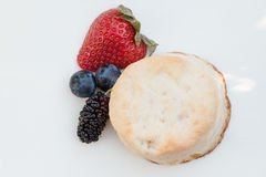 Scones with strawberries, blueberry and mulberry on wooden table Royalty Free Stock Photo
