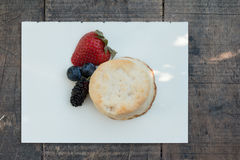 Scones with strawberries, blueberry and mulberry on wooden table Royalty Free Stock Images