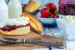 Scones with strawberry jam and clotted cream. Traditional English scones with strawberry jam and clotted cream Royalty Free Stock Images